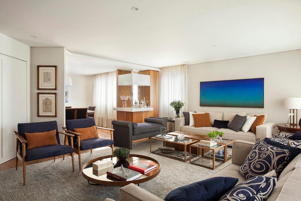 sala integrada em tons de azul e terra, com madeira, quadro solferini e bar