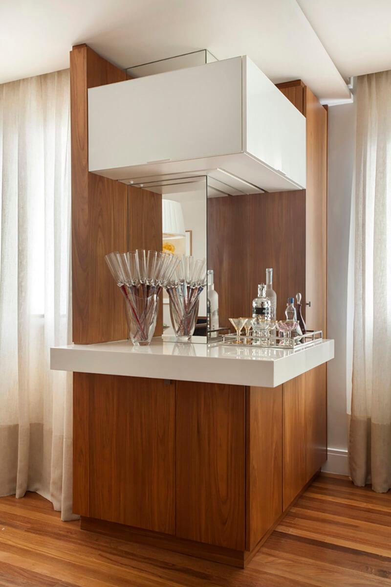 bar com marcenaria que ocultam os armarios para bebidas e copos. armario superior com portas em vidro branca e fitas de led iluminam a bancada. espelho