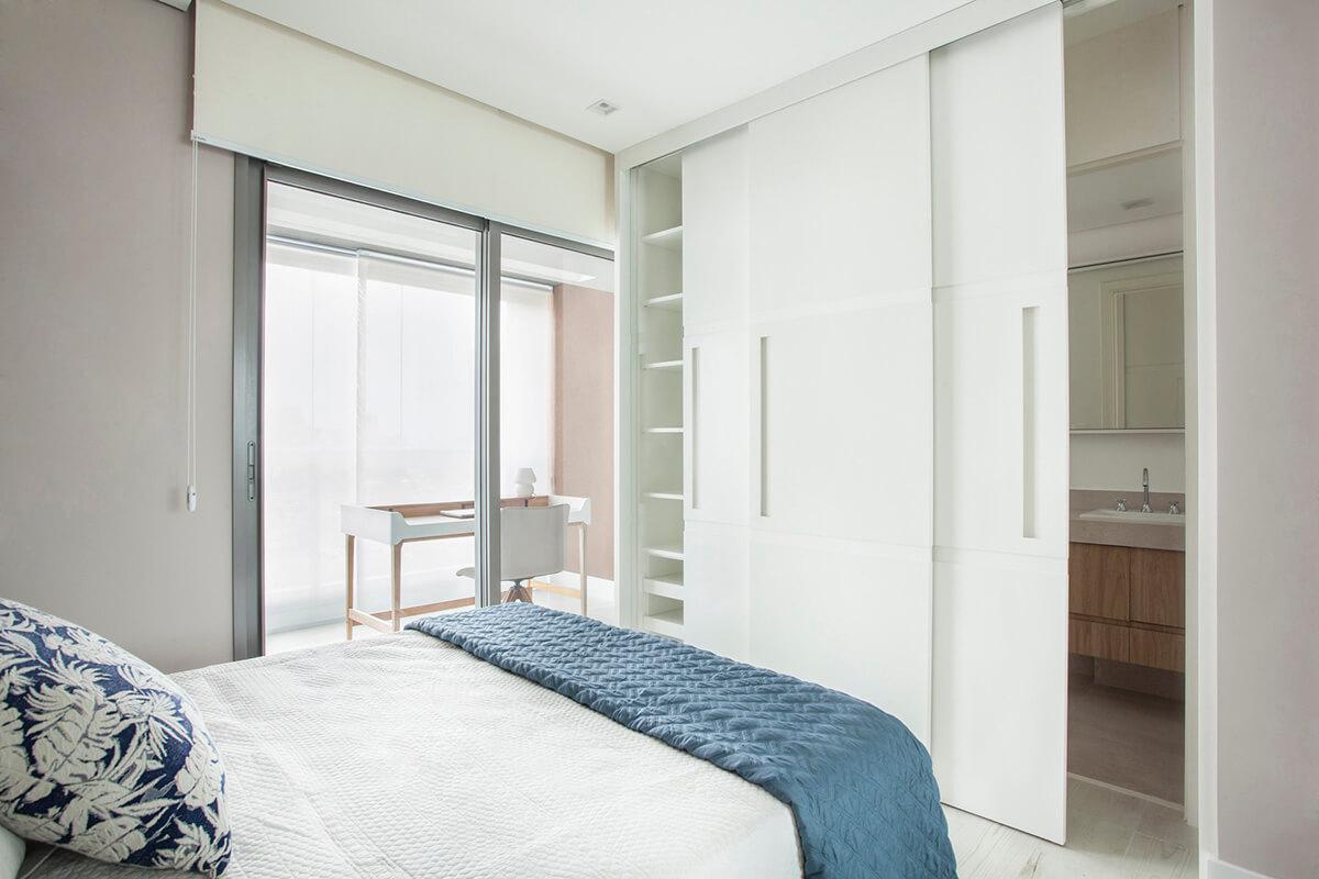 painel em laca branca ocultando armário e porta de banheiro