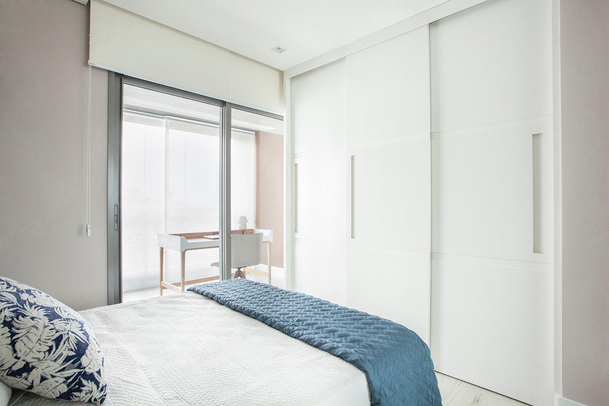 painel em laca branca ocultando armário e porta de banheiro- fechado