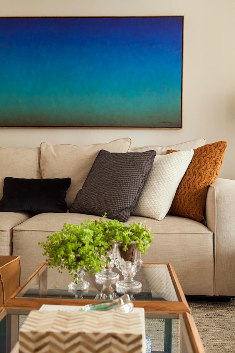 detalhes da sala em tons de azul e terra, com madeira, quadro solferini