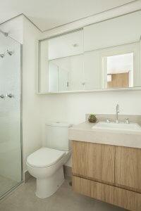 banho pequeno com espelhoem toda largura ocultando armario