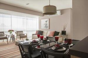 sala, varanda e cozinha integrados em apartemento pequeno com mesa de jantar e cadeiras preas tapete listrado,sofá e poltronas