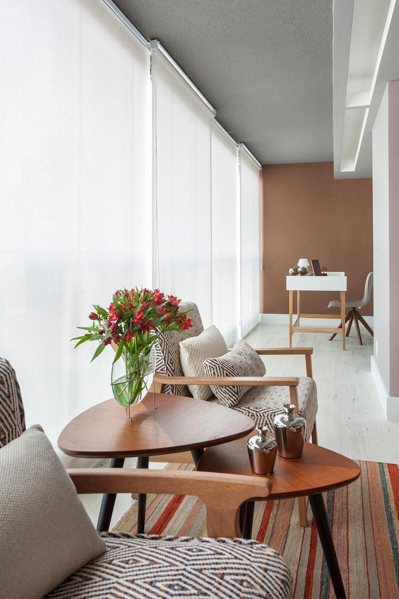 varanda integrada com a sala, com cantinho de trabalho com escrivaninha, poltronas com estrutura em madeira, tecido estampado, mesinha ninho triangular e tapete listrado colorido