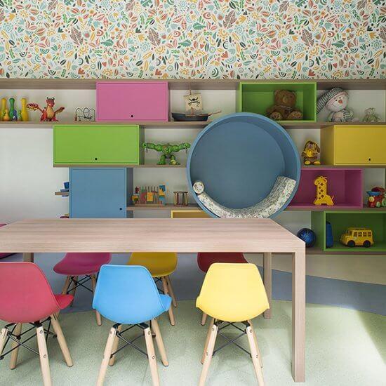 brinquedoteca colorida, casinha com estrutura de madeira, puffs coloridos,mesa em madeira com cadeiras eames infantil coloridas