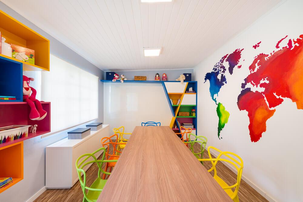 sala de estudos com marcenaria colorida e mapa mundi pintado na parede