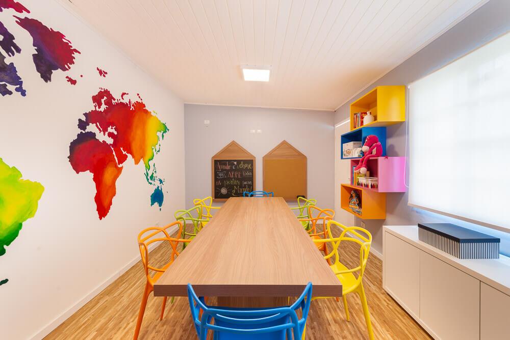 sala de estudos com mapa mundi degrade e marcenaria colorida, lousa e quadro de cortiça