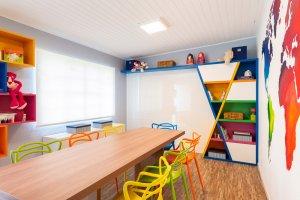 sala de estudos com marcenaria em nichos coloridos e mapa mundi na parede
