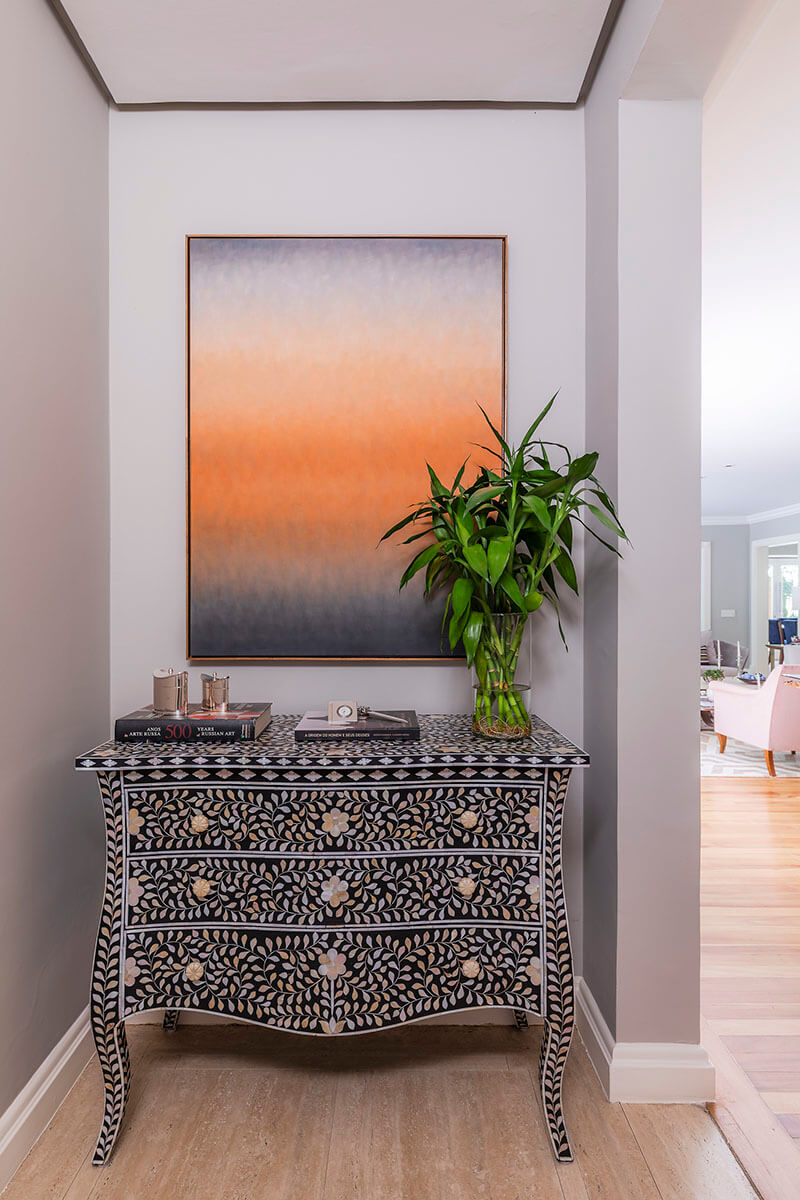 hall de entrada com comoda em marcetaria asiatica e quadro degradeem tons de laranja Solferini - Copia