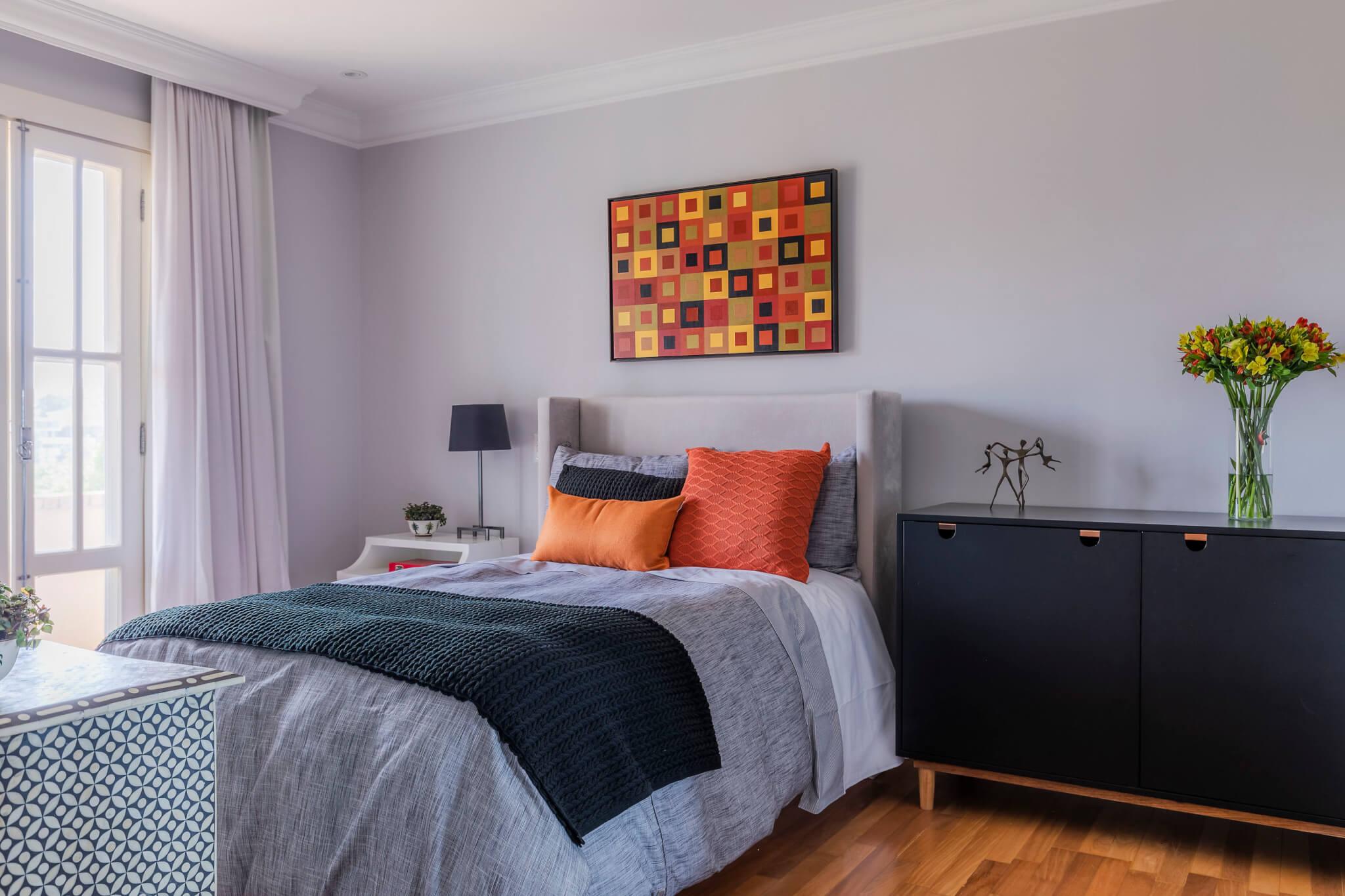 quarto de uma jovem com base neutra em tons de cinza e almofadas e quadros em laranja e amarelo 1