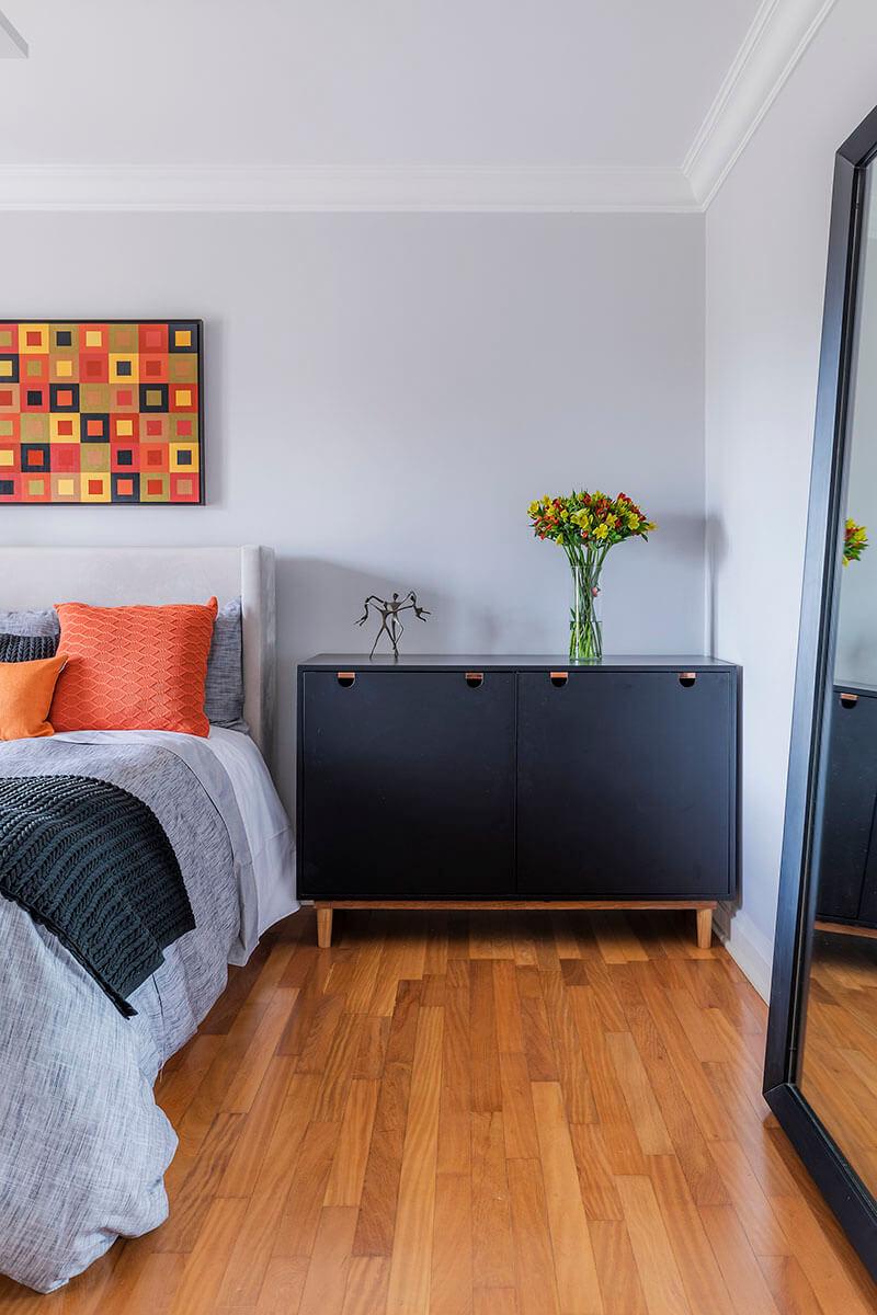 quarto de uma jovem com base neutra em tons de cinza e almofadas e quadros em laranja e amarelo