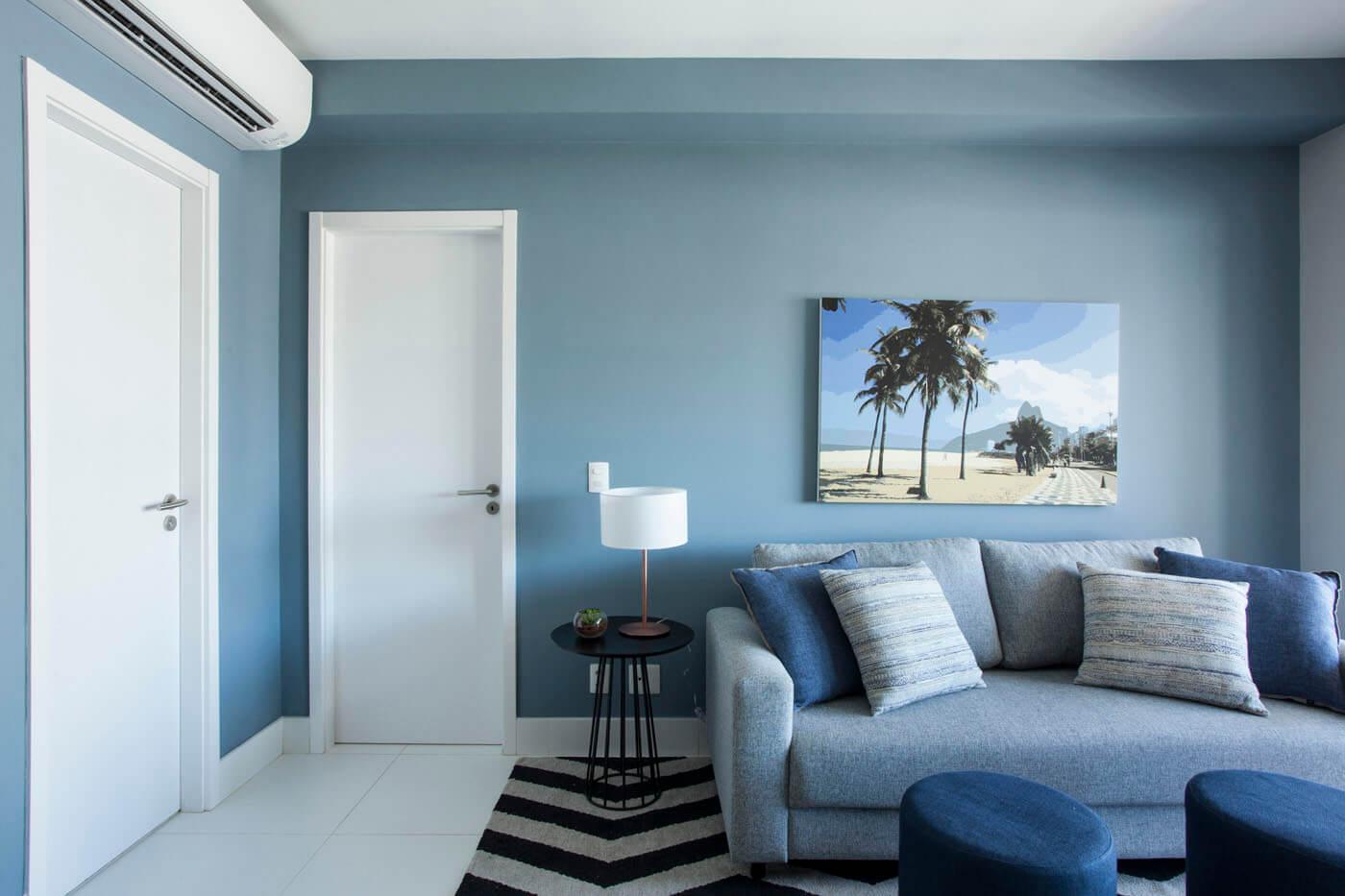 sala com parede azul, tapete geometrico e quadro do Rio de Janeiro 1