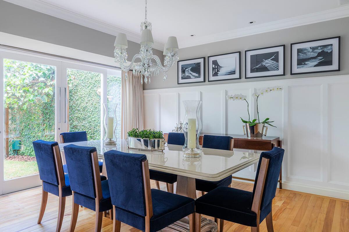sala de jantar com toques classicos, cadeira azul marinho, boiserie e fotografias do rio de janeiro e preto e branco