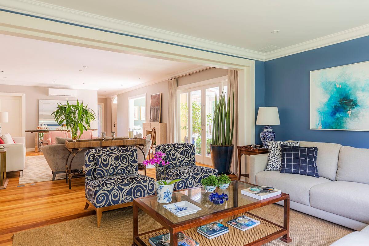 sala de tv com parede azul e telas abstratas Rosanna vaz