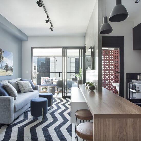 sala e cozinha integradas com painsel de Tv em cimento queimado e tapete chevron