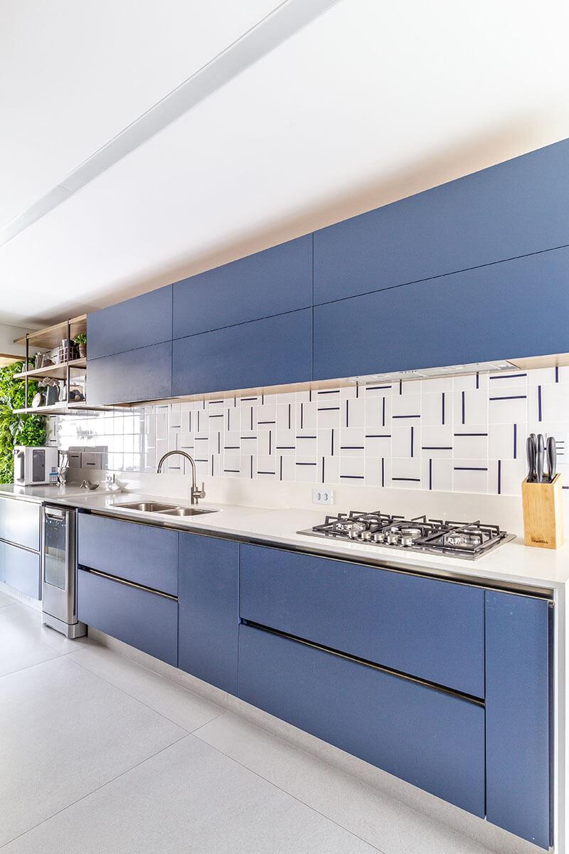 Cozinha com armários azuis e azulejos artesanais com delicados desenhos