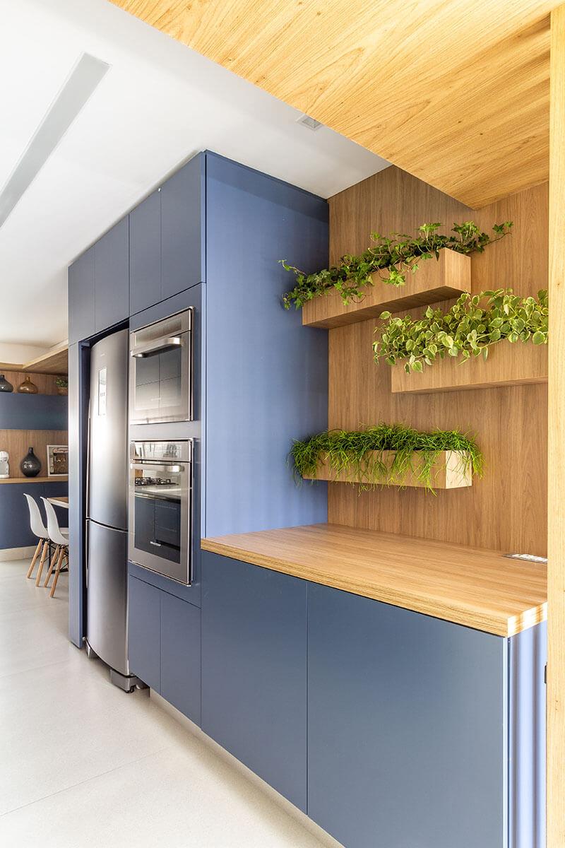 Detalhe de jardineiras na cozinha sobre painel de madeira na marcenaria azul