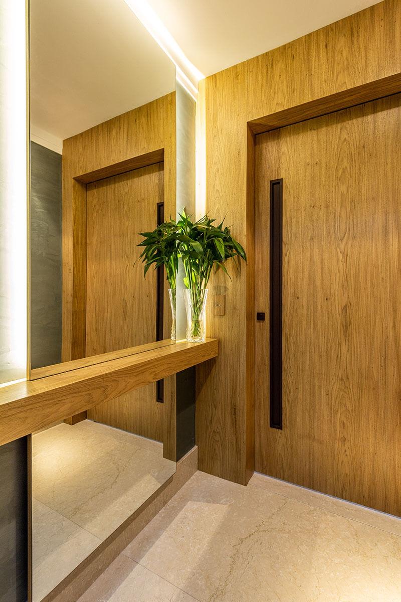 Hall de elevador com madeira e espelho