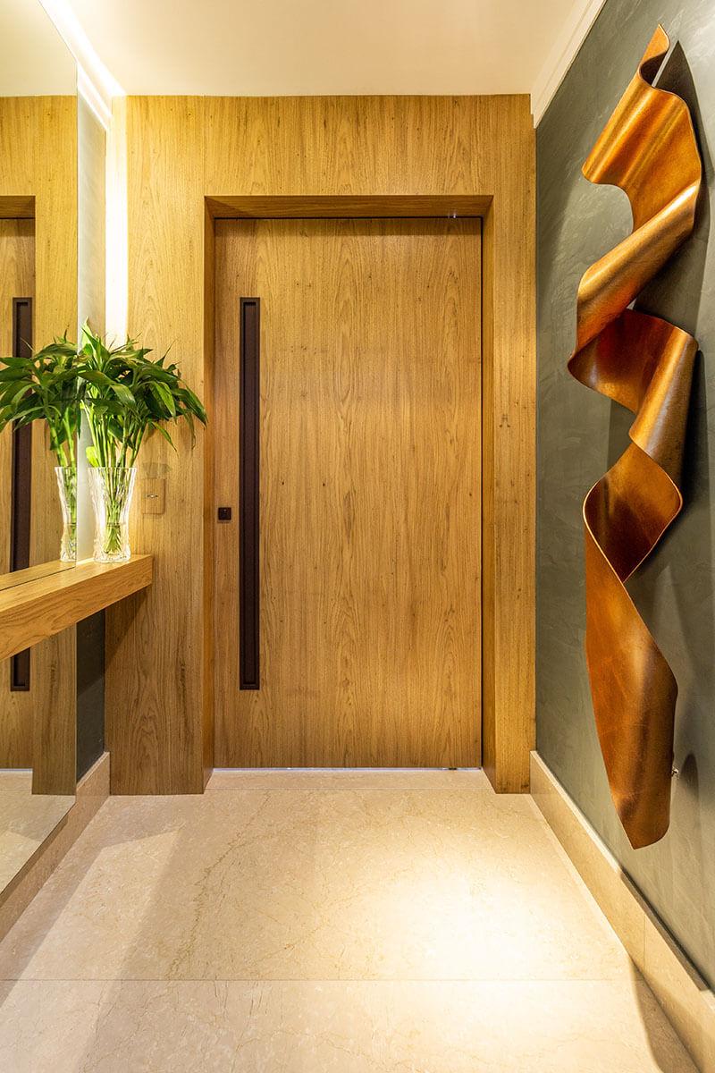 Hall de elevador com porta de madeira e escultura em resina cobre sobre paredes verdes