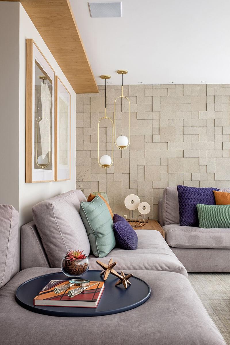 Varanda com revestimento 3D na parede e almofadas azul e ferrugem