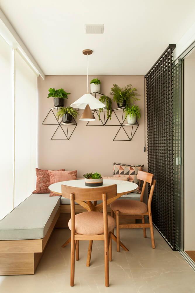 Charmoso cantinho com banco e mesa na varanda com parede rosê e mosaico de plantas
